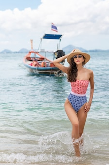 Beautiful woman in a swimsuit and hat standing in the sea. summer vacation. boat    .