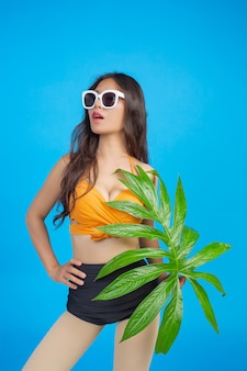 A beautiful woman in a swimsuit holding a green leaf poses on blue