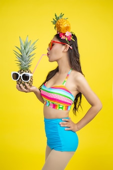 Beautiful woman in a swimsuit holding a pineapple poses on yellow