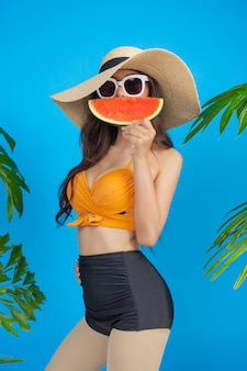 Beautiful woman in a swimsuit holding a watermelon on blue