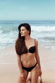 Beautiful woman in swimwear on the beach. portrait of pretty female with slim tanned sexy body in black bikini . summer lifestyle. vacation