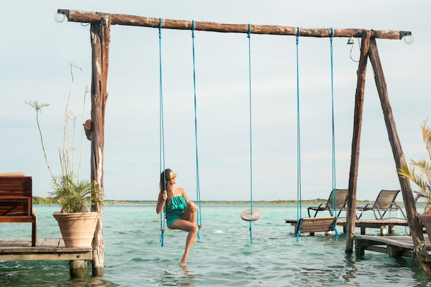 Beautiful woman on the swings which above a water