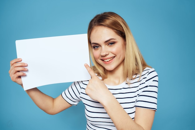Beautiful woman in a t-shirt holds a white sheet without an inscription, free space, empty space, copy space