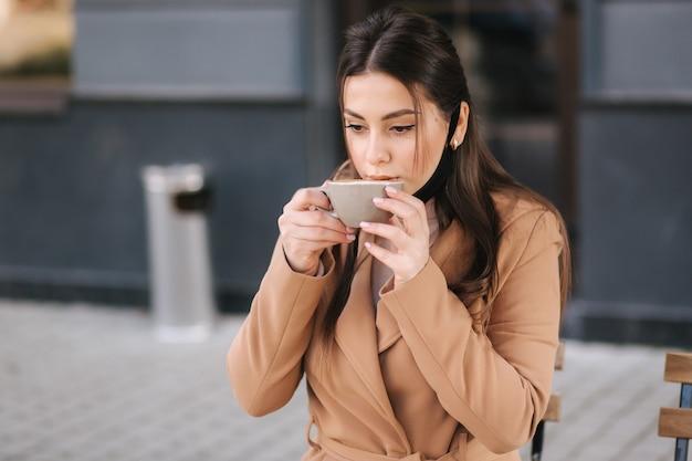 아름 다운 여자는 커피를 마시는 보호 마스크를 벗습니다. 여성 야외 테라스와 음료 커피에 앉아.