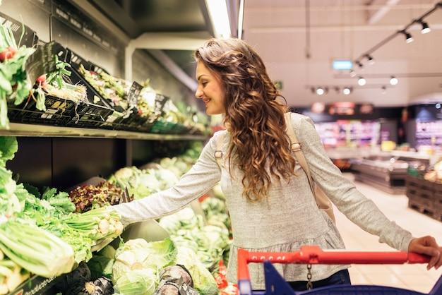 슈퍼마켓에서 상 추를 복용하는 아름 다운 여자. 시장 식품 개념.