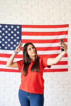 미국 국기 배경에 selfie를 복용하는 아름 다운 여자