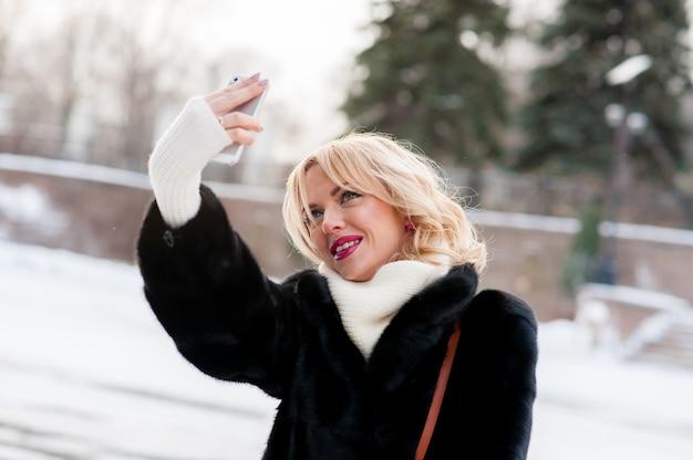 Красивая женщина, делающая зимнее селфи на открытом воздухе