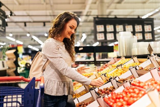 슈퍼마켓에서 음식을 복용하는 아름 다운 여자. 시장 식품 개념.