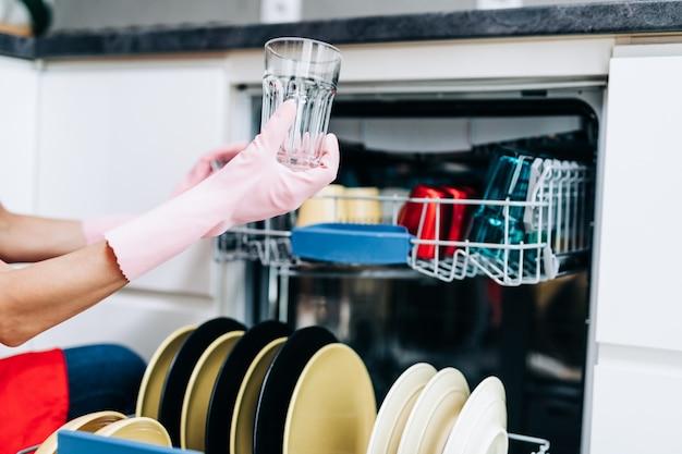 Красивая женщина, вынимая чистую посуду из посудомоечной машины.