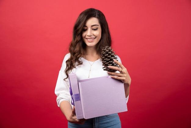 보라색 선물 상자에서 pinecone를 복용하는 아름 다운 여자. 고품질 사진