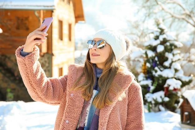 雪に覆われたリゾートでselfieを取る美しい女性