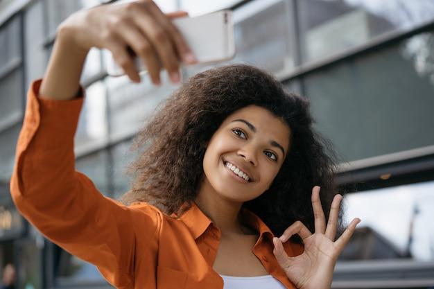 Selfieを取って、携帯電話を手で押し、okの標識を示す美しい女性。若いブロガーがオンラインでビデオをストリーミング