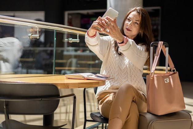 Красивая женщина, делающая селфи, использует смартфон, позирующий в терминале международного аэропорта перед вылетом