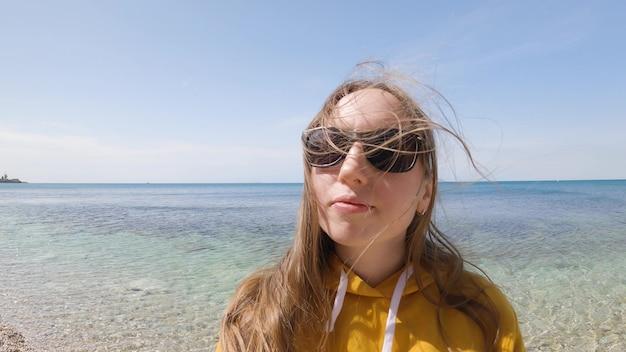 日没時にビーチで携帯電話を使用してselfieを取っている美しい女性は、休暇で自然とライフスタイルを楽しんで笑顔と回転します。