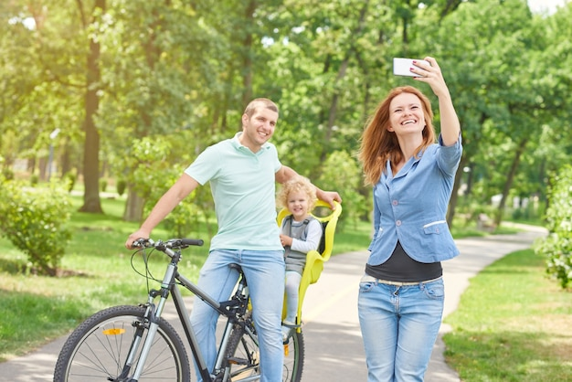Beautiful woman taking selfie with husband and baby on bicycle while relaxing outdoors at park.