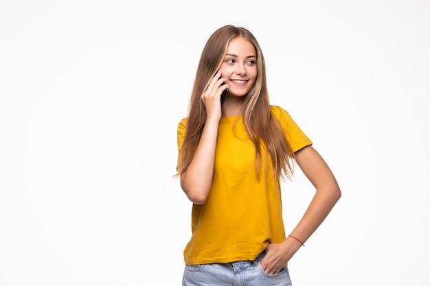흰 벽에 고립 된 휴대 전화에서 말하는 아름 다운 여자