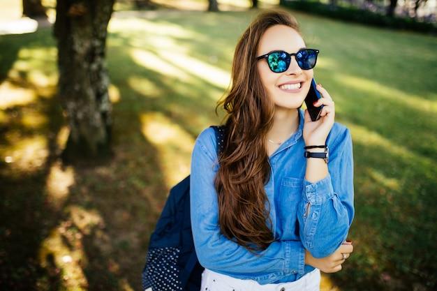 Bella donna che parla al cellulare nel parco estivo