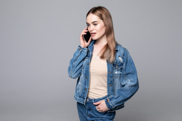 Beautiful woman talking on mobile phone on the gray wall