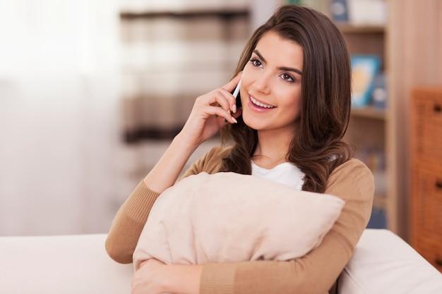 Bella donna che parla sul telefono cellulare a casa