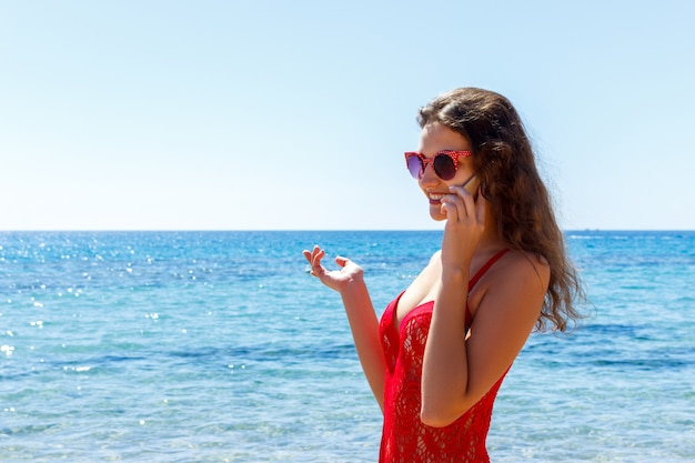 Beautiful woman talking on the mobile phone on the sea