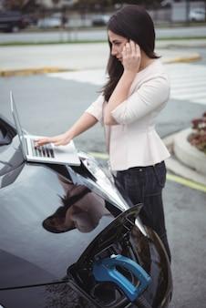 전기 자동차를 충전하는 동안 휴대 전화에 말하는 아름 다운 여자