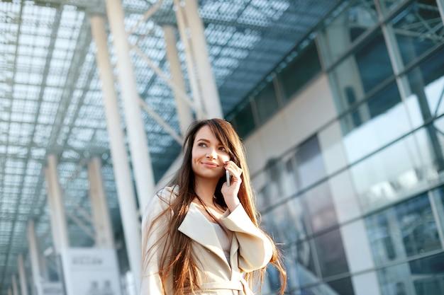 거리에 걷는 전화 통화하는 아름 다운 여자. 모바일 전화 유행 옷에 세련 된 미소 비즈니스 여자의 초상화