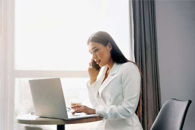 Beautiful woman talking on phone while  working on laptop computer sitting at home managing her business via home office during coronavirus or covid-19 quarantine