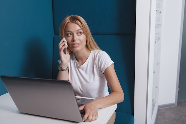 Beautiful woman talking on the phone while working on laptop