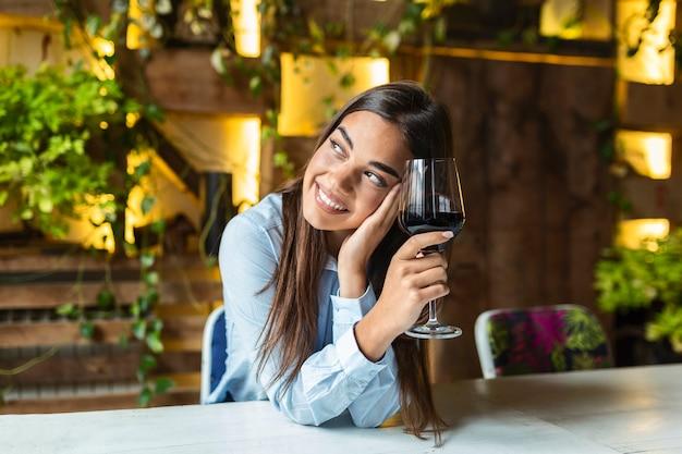 레스토랑에 앉아있는 동안 와인을 시음하는 아름 다운 여자. 유리를 잡고 와인을 마시는 카페에 앉아 귀여운 예쁜 젊은 여자의 이미지. 아름 다운 와인 시음 관광 여자의 초상화.