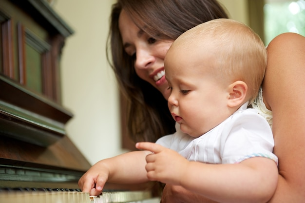 Beautiful woman teaching baby to play piano