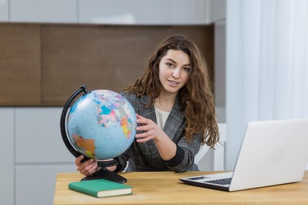 家で座ってオンラインで教える美しい女性