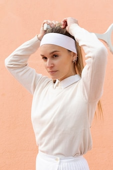 Beautiful woman tennis player grabs hair tail