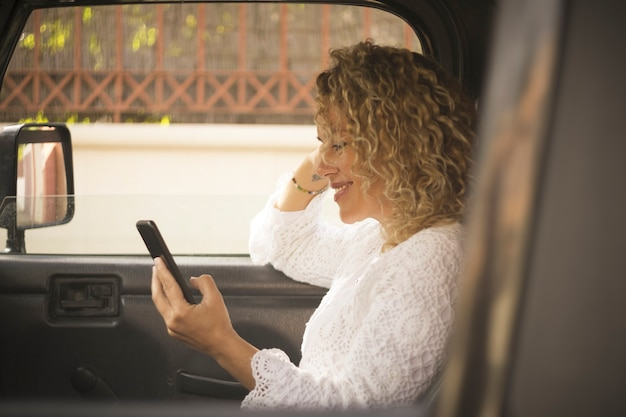 車の中で座っている携帯電話を使用して美しい女性のテキストメッセージやメディアコンテンツを見ています。車の中で携帯電話を持つ幸せな女性。ソーシャルメディアのコンテンツをオンラインで見て携帯電話を操作する笑顔の女性