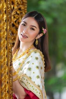 Bella donna in abito tradizionale tailandese sorridente e in piedi al tempio