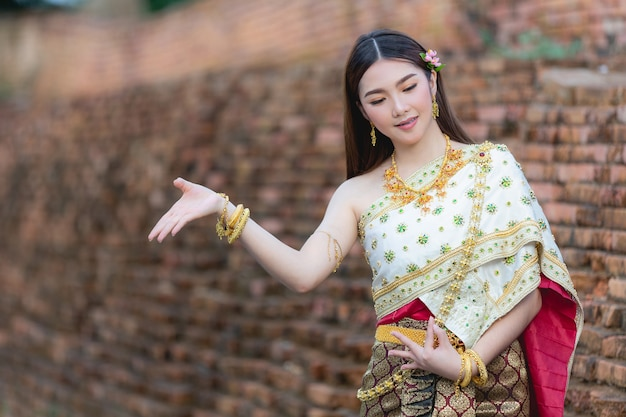 Beautiful woman in thai traditional outfit smiling and standing at temple