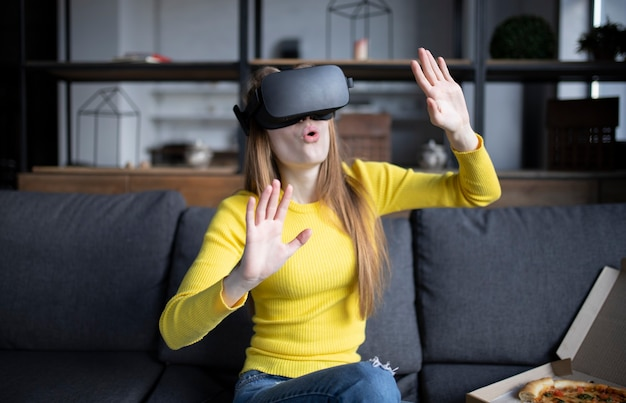 Beautiful woman touching air during the vr experience. girl eats pizza