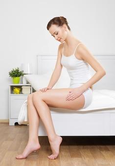 Красивая женщина, касаясь ее гладкого бедра здоровья, сидя на кровати