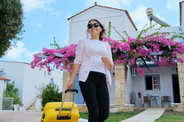 Туристическая красивая женщина гуляет с чемоданом на территории курортного спа-отеля. белые синие гостиничные дома, цветущее садоводство с фоном розовых цветов. путешествие, отпуск, досуг, выходные, люди