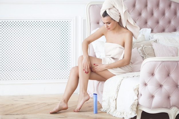 Beautiful woman in the towel after bathing applying body lotion