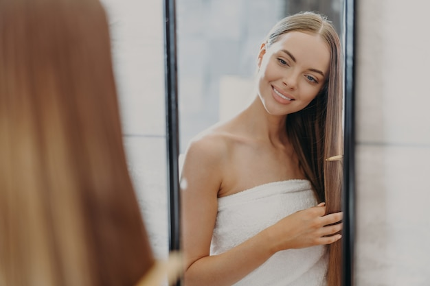 Beautiful woman in towel brushing her hair