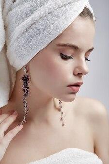 Beautiful woman in towel and earrings