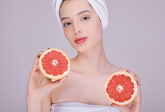 Beautiful woman in a towel holds two grapefruit in her hands.