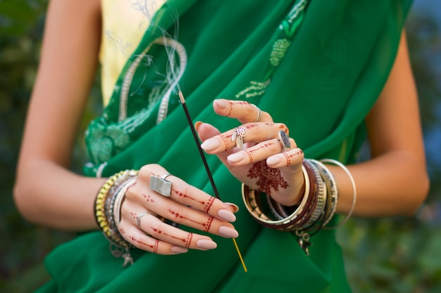 Beautiful woman in traditional muslim indian wedding green sari dress hands with henna tattoo mehndi pattern jewelry and bracelets hold burning aroma sticks summer culture festival celebration concept