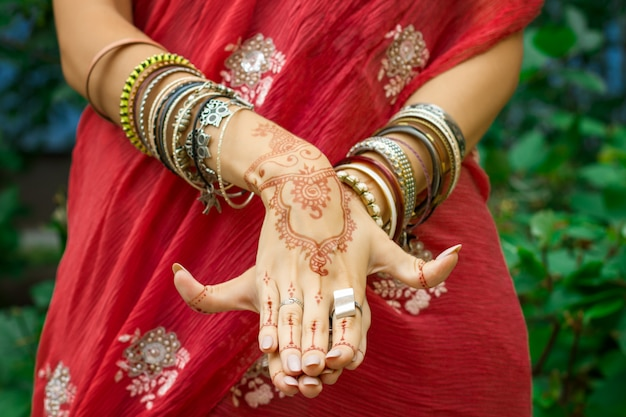 Beautiful woman in traditional muslim indian wedding pink red sari dress with henna tattoo jewelry, bracelets do hands nritta odissi samyuta hasta mudras dance movement matsya fish concept background