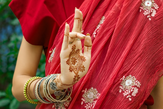 Beautiful woman in traditional muslim indian wedding pink red sari dress with henna tattoo jewelry bracelets do hands nritta odissi samyuta hasta mudras dance movement tripataaka concept background