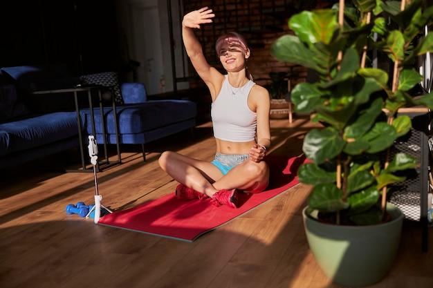 美しい女性のトレーナーは、自宅の携帯電話の近くの明るい日光から隠れています