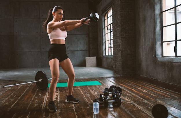Красивая женщина тренируется и делает функциональную тренировку в тренажерном зале