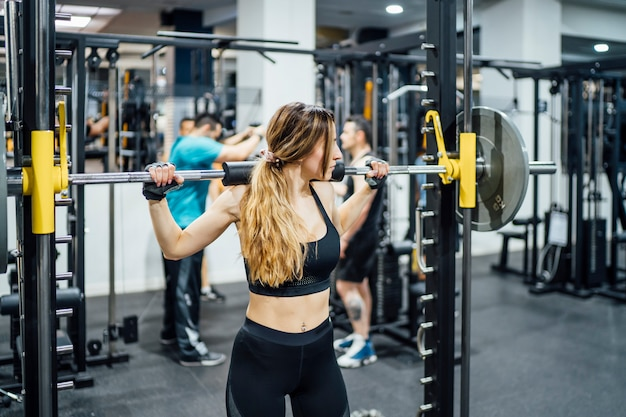 Beautiful woman training weights in gym