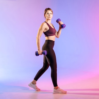 Beautiful woman training with weights