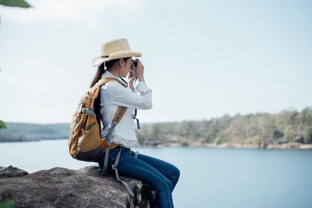 Beautiful woman traveler photographing temples